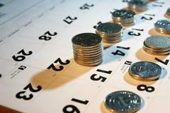 Monedas/dinero en un calendario Fotos de archivo libres de regalías