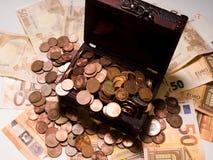 Monedas en caja y euros fotos de archivo libres de regalías
