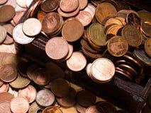Monedas en caja y euros foto de archivo