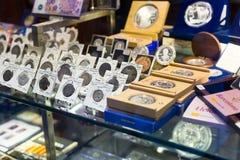 Monedas en contador en la tienda de la numismática Fotografía de archivo libre de regalías