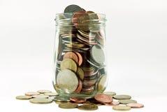 Monedas en el tarro de cristal Fotografía de archivo libre de regalías