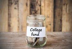 Monedas en el tarro de cristal del dinero con la etiqueta del fondo de la universidad, concentrado financiero Fotografía de archivo libre de regalías