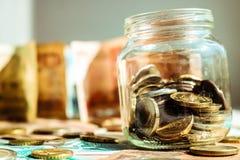 Monedas en el tarro de cristal Fondo del concepto con las monedas y los billetes de banco foto de archivo