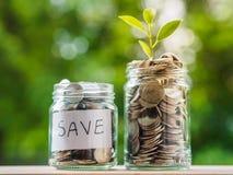 Monedas en el tarro de cristal en fondo de la falta de definición dinero que ahorra el co financiero fotografía de archivo libre de regalías