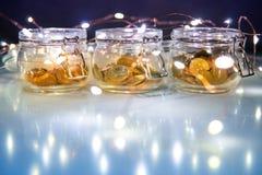 Monedas en el tarro de cristal de la moneda con las luces de la Navidad imágenes de archivo libres de regalías