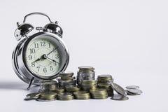 Monedas en el tarro y el dinero de cristal por otra parte con el reloj en el fondo aislado blanco para el negocio, finanzas, conc imagen de archivo