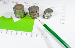 Monedas en fondo verde de los gráficos y de las cartas con el lápiz dinero a Imagenes de archivo