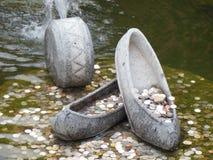 Monedas en fuente con los zapatos de piedra fotografía de archivo