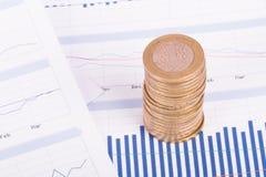 Monedas en gráficos de la carta y datos financieros imagenes de archivo