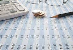 Monedas en la hoja de cálculo con el lápiz y la calculadora Fotos de archivo