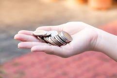 Monedas en las manos que ahorran, casa del mercado del dividendo de la caridad de la ayuda financiera del fondo de inversión de l Foto de archivo libre de regalías