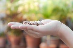 Monedas en las manos que ahorran, casa del mercado del dividendo de la caridad de la ayuda financiera del fondo de inversión de l Fotos de archivo libres de regalías