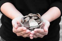 Monedas en las manos que ahorran, casa del mercado del dividendo de la caridad de la ayuda financiera del fondo de inversión de l Foto de archivo