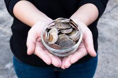 Monedas en las manos que ahorran, casa del mercado del dividendo de la caridad de la ayuda financiera del fondo de inversión de l Imagenes de archivo