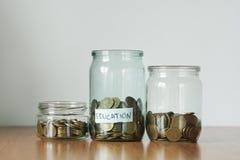 Monedas en los tarros de cristal para diversas necesidades, cajas de dinero Distribución del concepto de los ahorros del efectivo imágenes de archivo libres de regalías