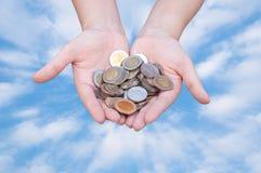 Monedas en manos en el cielo azul Fotos de archivo