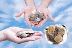 Monedas en manos en el cielo azul Imagen de archivo libre de regalías