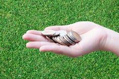Monedas en manos en hierba Foto de archivo libre de regalías