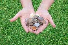 Monedas en manos en hierba Foto de archivo