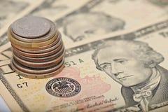 Monedas en notas del dólar Imagenes de archivo