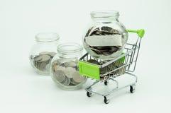 Monedas en pequeño concepto financiero del envase y del carro de compras Fotografía de archivo