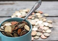 Monedas en taza Fotografía de archivo libre de regalías