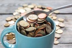 Monedas en taza Imagen de archivo libre de regalías