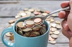 Monedas en taza Fotos de archivo