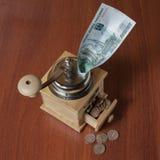 Monedas en un molino del cofee Imágenes de archivo libres de regalías