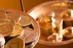 Monedas en un peso de la escala Foto de archivo libre de regalías