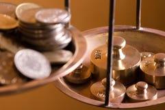 Monedas en un peso de la escala Imagen de archivo libre de regalías