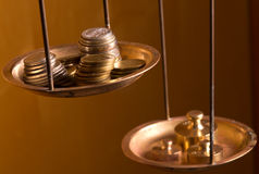 Monedas en un peso de la escala Imágenes de archivo libres de regalías