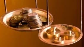 Monedas en un peso de la escala Imagen de archivo