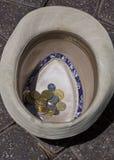 Monedas en un sombrero Imágenes de archivo libres de regalías