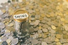 Monedas en un tarro de cristal con el ` escrito nota del AHORRO del ` Foto de archivo