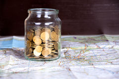 Monedas en un tarro en un mapa contra fondo de madera oscuro Copie el balneario Imagen de archivo