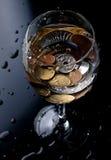 Monedas en un vidrio Fotos de archivo