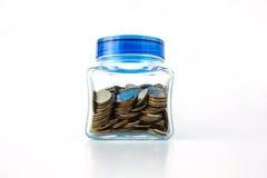 Monedas en una botella de cristal Fotos de archivo