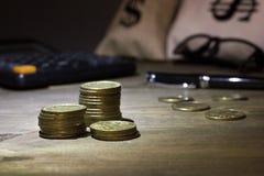 Monedas en una columna, y bolso del fondo del scatteredthe con un dólar fotografía de archivo