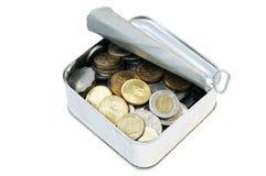 Monedas en una poder de estaño Foto de archivo libre de regalías