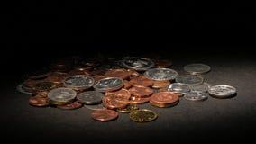Monedas en una superficie oscura Manche la luz almacen de video