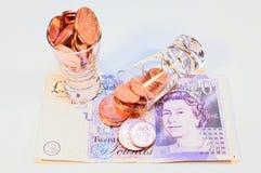monedas en vidrio en billetes de banco británicos Fotografía de archivo libre de regalías