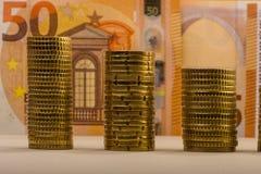 Monedas euro apiladas contra una denominación de papel digno del euro cincuenta Imagen de archivo libre de regalías