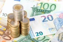 Monedas euro apiladas en fondo euro de los billetes de banco Fotos de archivo libres de regalías