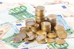 Monedas euro apiladas en fondo euro de los billetes de banco Fotografía de archivo libre de regalías