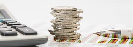 Monedas euro apiladas en la hoja de la tabla Foto de archivo