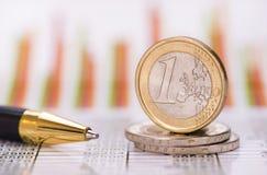 Monedas euro apiladas sobre datos del mercado de intercambio Fotos de archivo libres de regalías