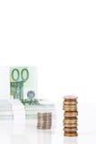 Monedas euro apiladas y billetes de banco euro en un fondo blanco Foto de archivo