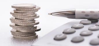 Monedas euro con la calculadora y la pluma Foto de archivo