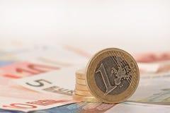 Monedas euro de la columna en billetes de banco euro Imagenes de archivo